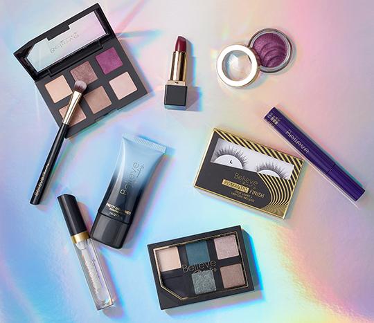 metallic background with eyeshadow, lip stick, mascara, eyelashes laid out