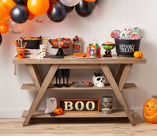 Halloween décor and party items on a shelf with balloons and candy