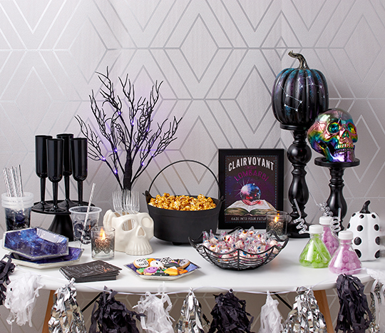 Black and purple mystic Halloween décor on a party table with snacks and treats.