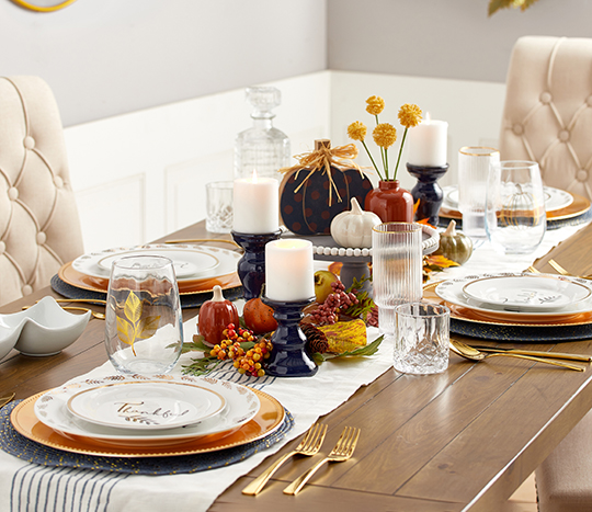 dining table with place settings and decorative accents, candles and cake stand