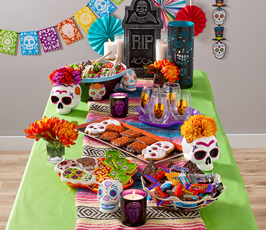bright sugar skull décor and party treats on table